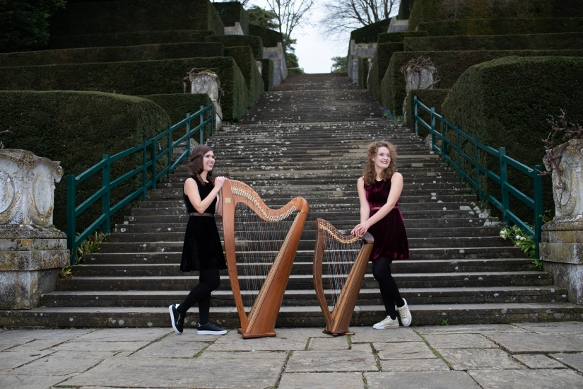 Two harpists standing by harps in front of staircase outdoors, left harp is bigger than the right harp.