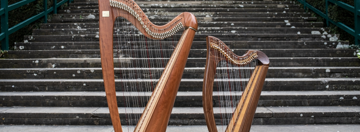 Two harps in front of a large stone staircase, Eos harp on the left is bigger, 27 string harp on the right