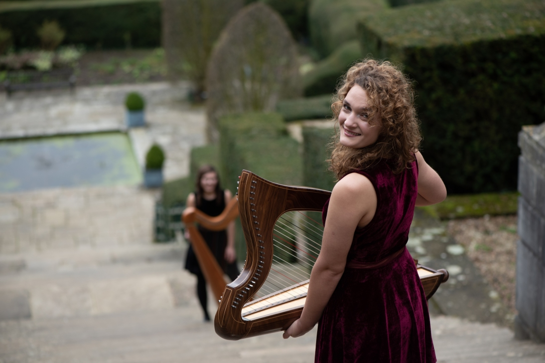 Wedding harpist standing on roman steps at Port Lympne Hotel and reserve, below is second musician with large harp