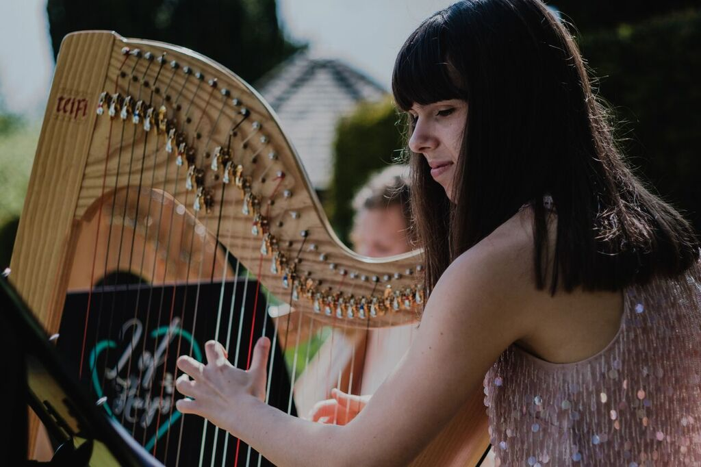 Close up image of a a harpist looking at music performing at wedding ceremony outside