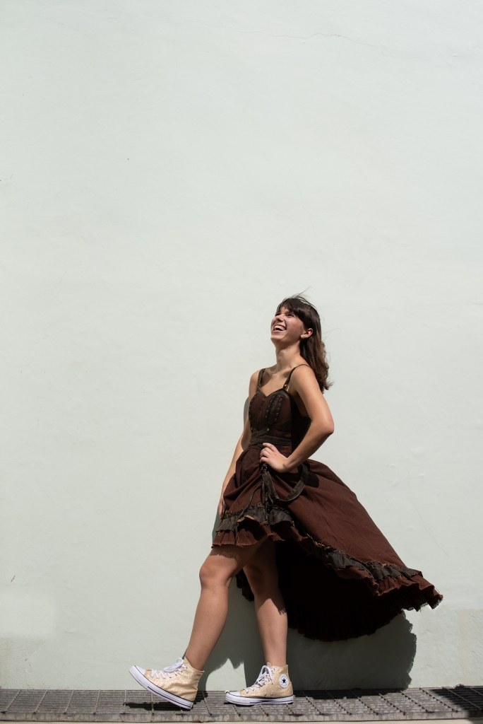 Adel Wilson in a steam punk dress in Sandgate by a white wall