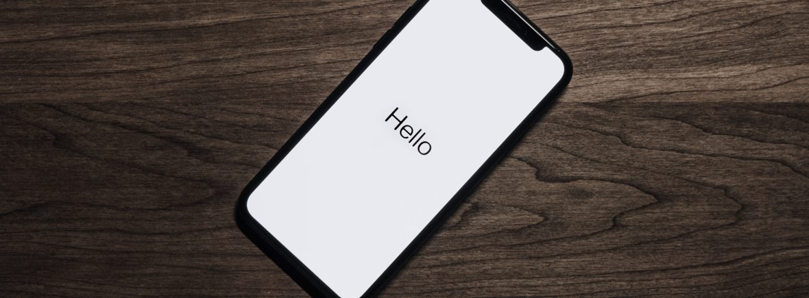 Smart phone laying on wood, white phone case reads 'Hello'