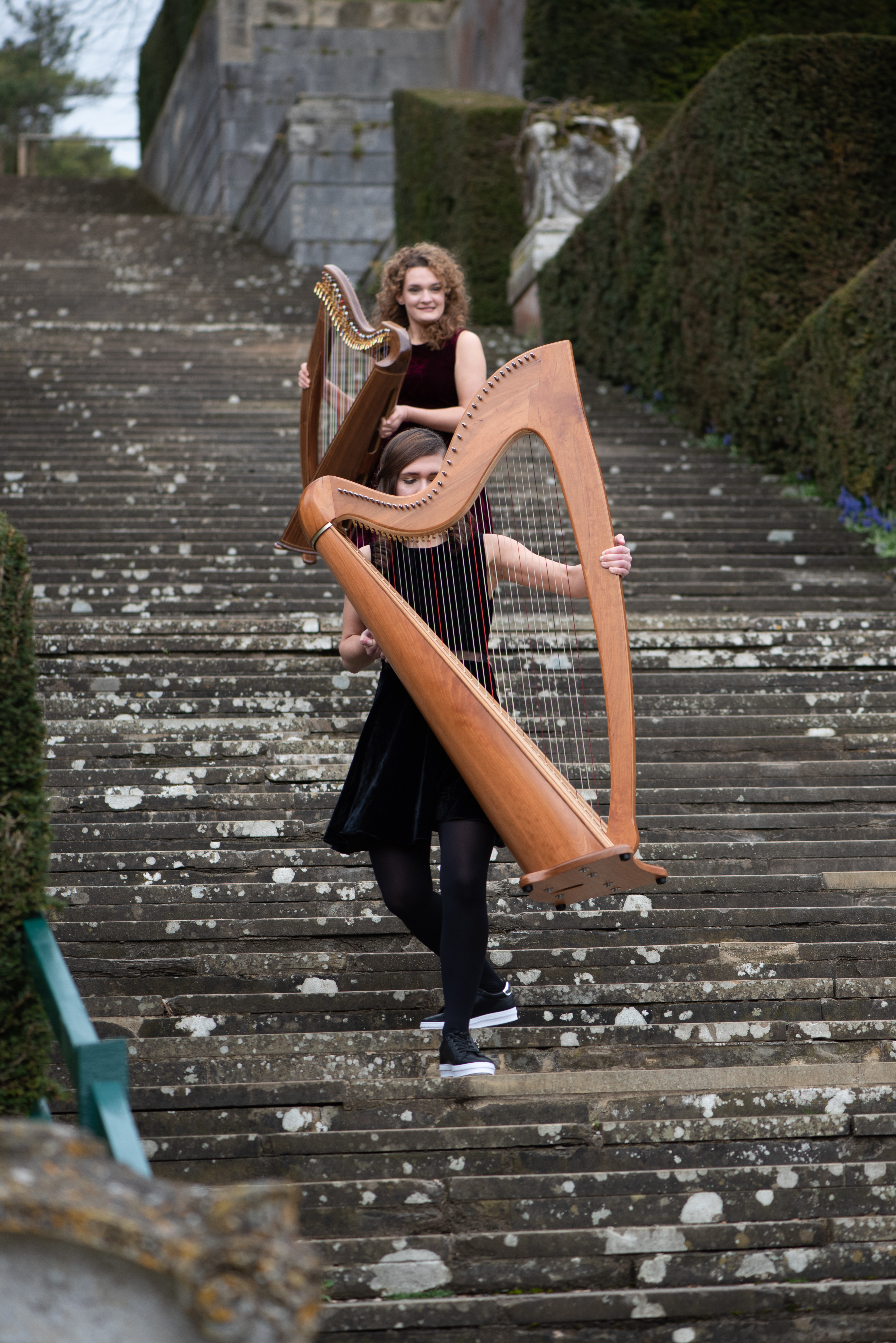 Adel, harpist carrying harp down staircase, Karina behind Adel with small harp