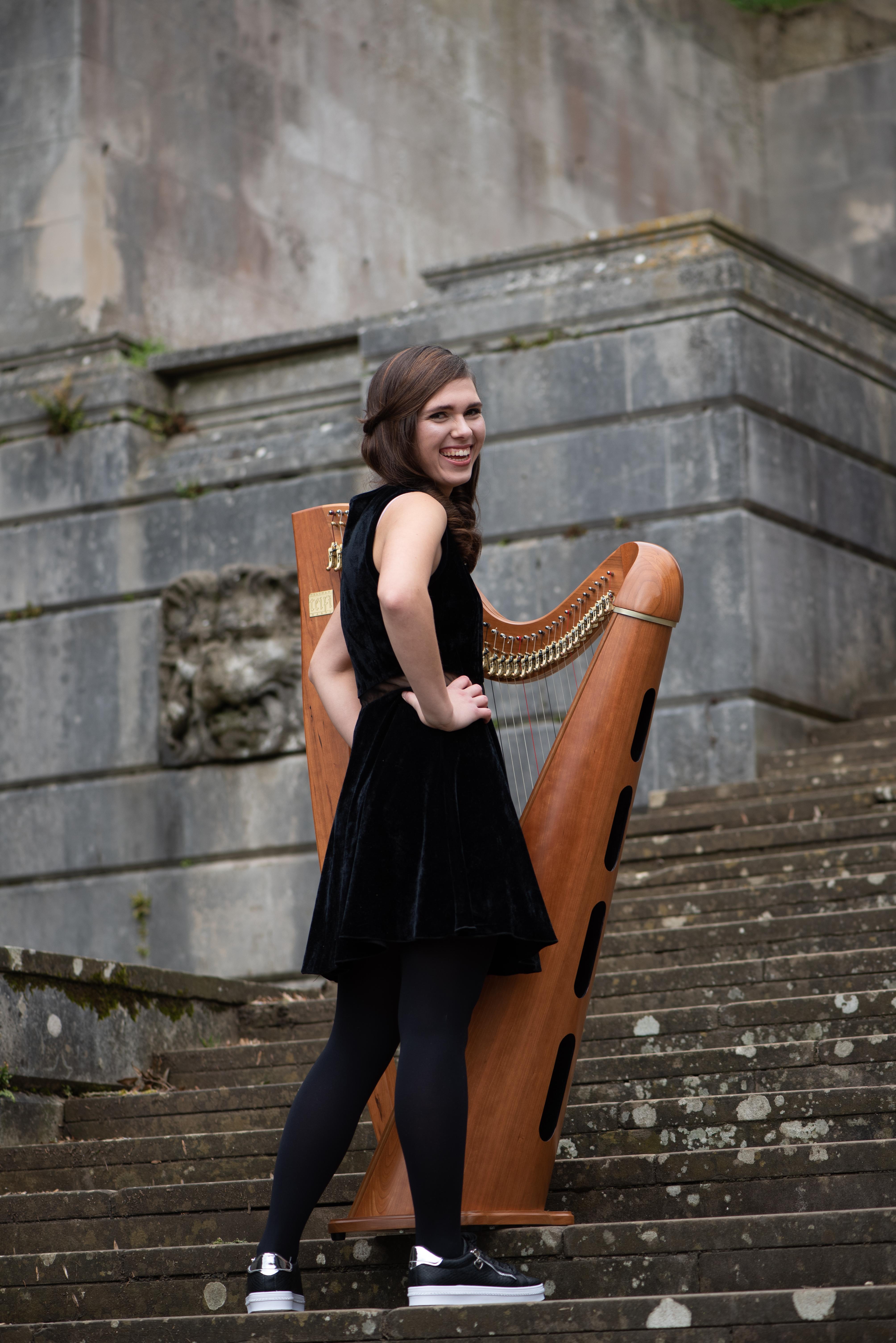 Adel, wedding harpist standing in front of harp