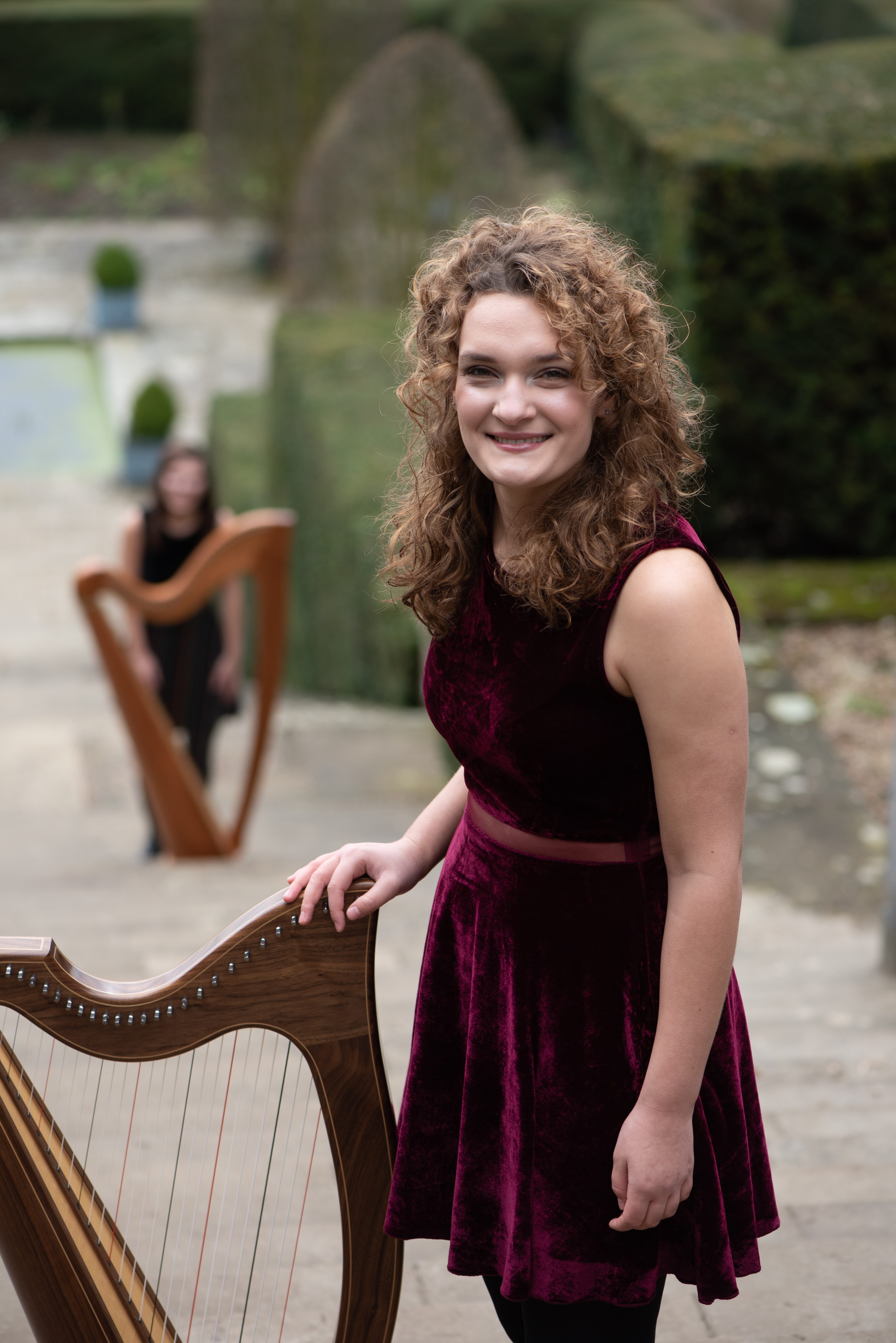 Karina, Harpist standing at the top of a staircase with Adel harpist in the background bl