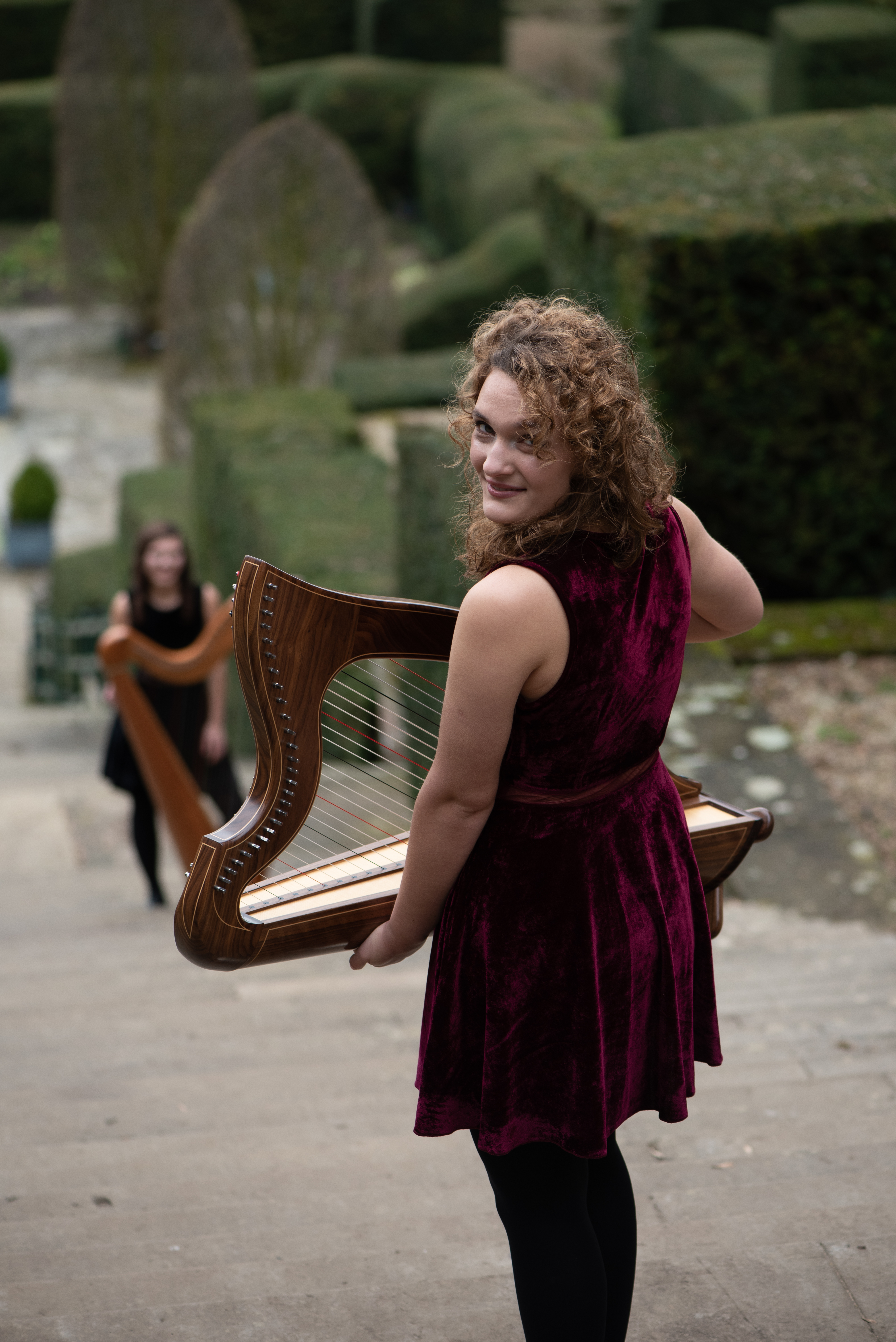Karina looking over her shoulder holing a small harp, Adel in the background with a