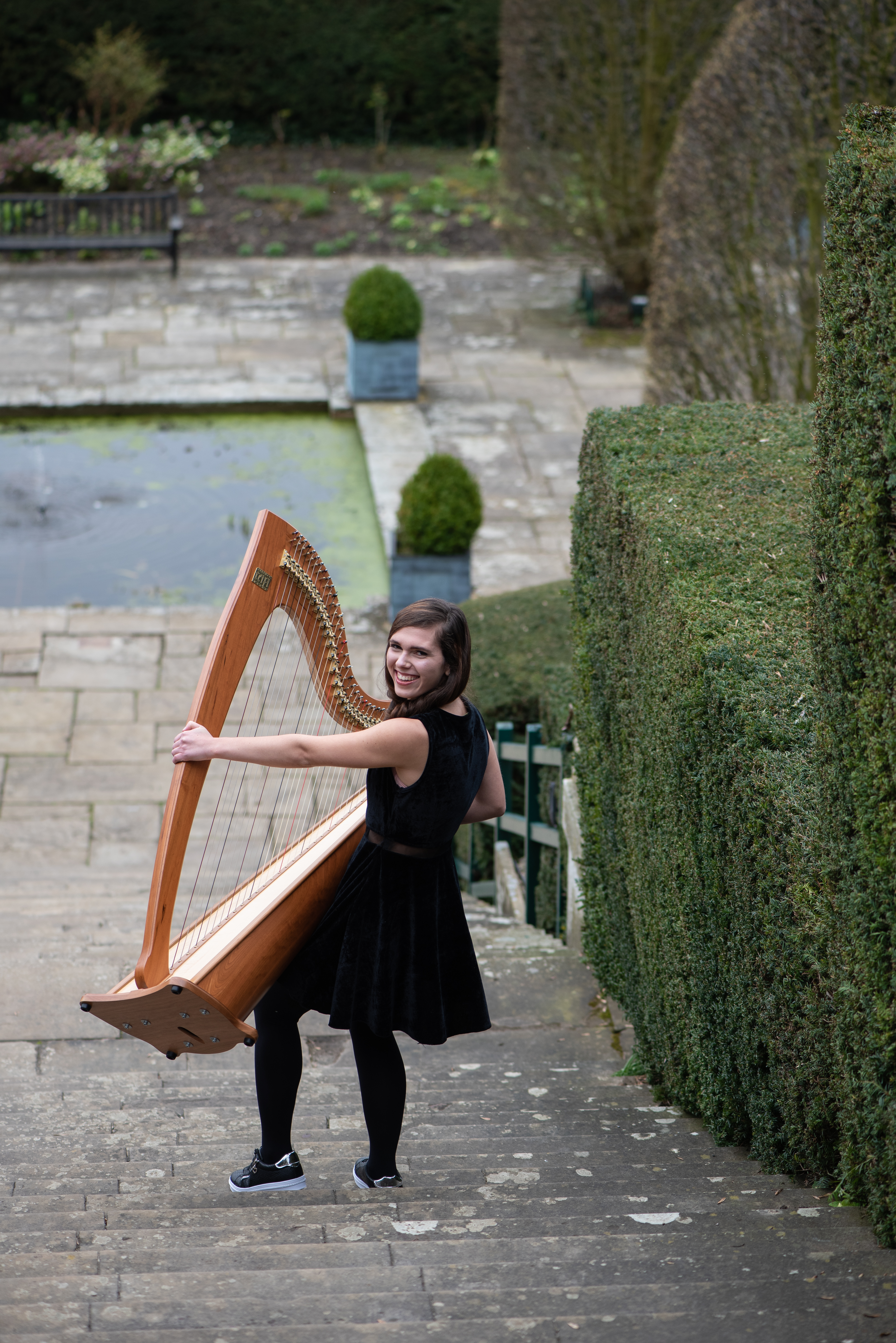 wedding harpist Adel carrying a harp down stairs outside Port Lympne Hotel and Resrev
