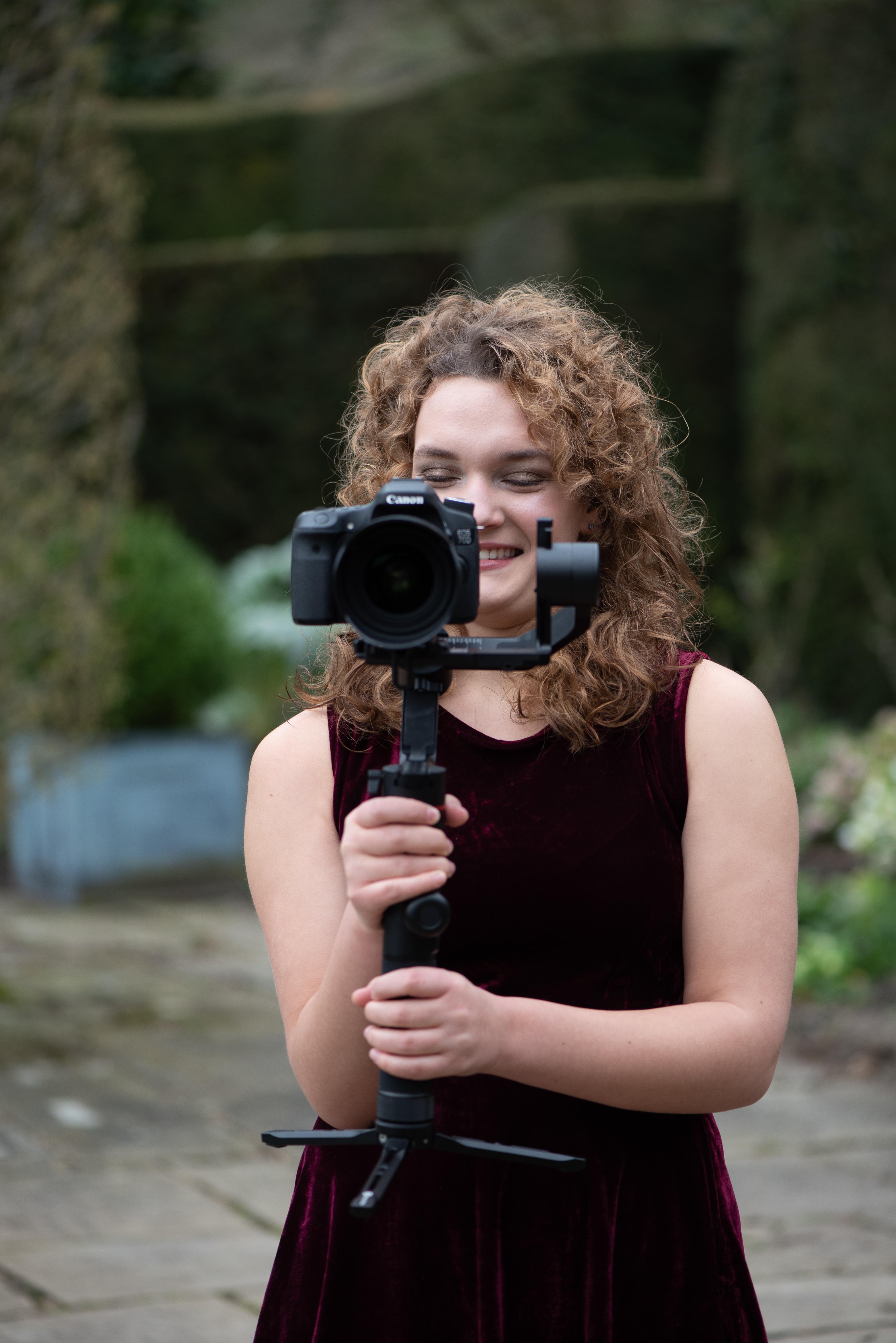 Karina, harpist holding a video camera