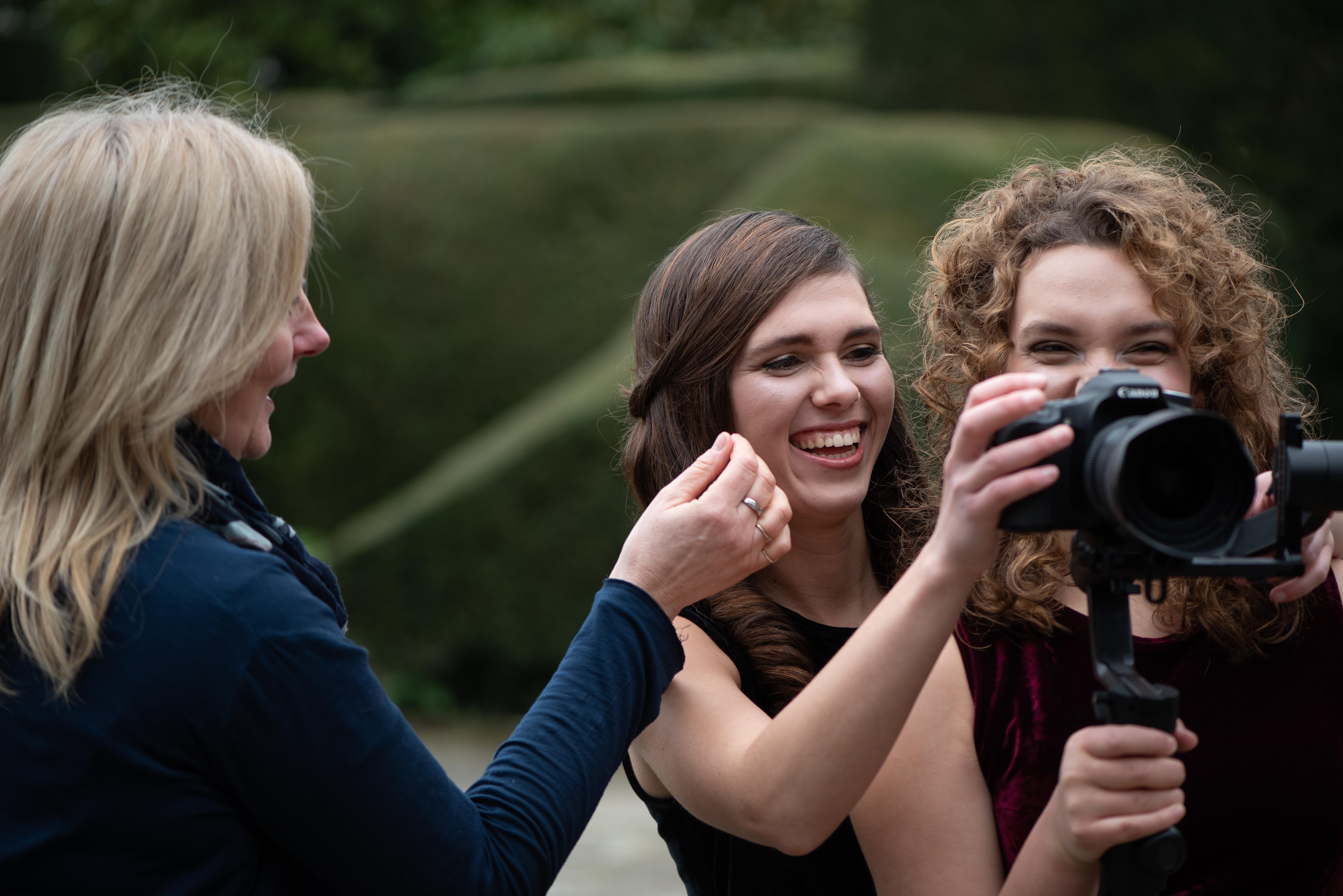 Harpists Karina and Adel holding a video camera, Gillian Smissen, doing makeup